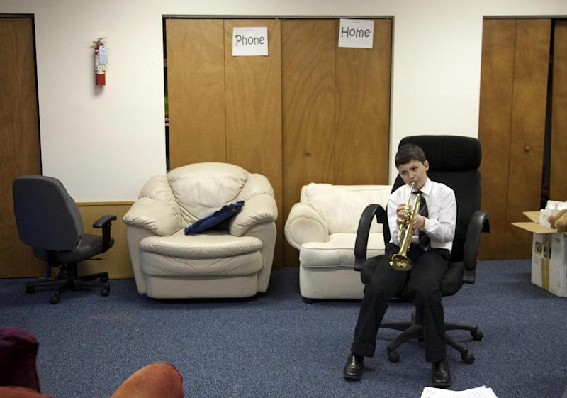 Joshua Bannon, 11, practices his trumpet solo in the basement of the Salvation Army before the Alexandria School for the Performing Arts winter recital, Sunday, March 11, 2012, in Alexandria, Va. A survey of Salvation Army youth programs in more than 80 cities shows more than eight in 10 programs saw increased demand from children and families in the past year as the nation's high jobless rate and cutbacks in government and private funding strained charities. The survey released to The Associated Press found 56 percent of the charity's youth programs _ including camps, preschools, daycare and after-school programs _ are operating at or beyond their capacity.(AP Photo/Carolyn Kaster)