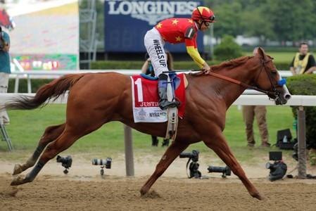 FILE PHOTO: Jockey Mike Smith smiles as he rides Justify across the finish line to win the 150th running of the Belmont Stakes, the third leg of the Triple Crown of Thoroughbred Racing at Belmont Park in Elmont, New York