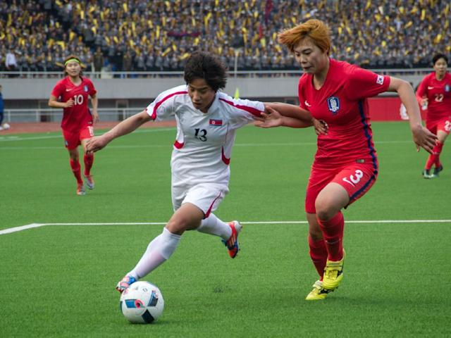 Ri Kyong-Hyang of North Korea fights for the ball with Shin Damyeong (AFP/Getty )