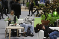 Two participants catch up with some sleep at the COP25 summit in Madrid, Spain, Tuesday, Dec. 10, 2019. The 2-week global U.N. sponsored climate change conference is taking place in Madrid. (AP Photo/Paul White)