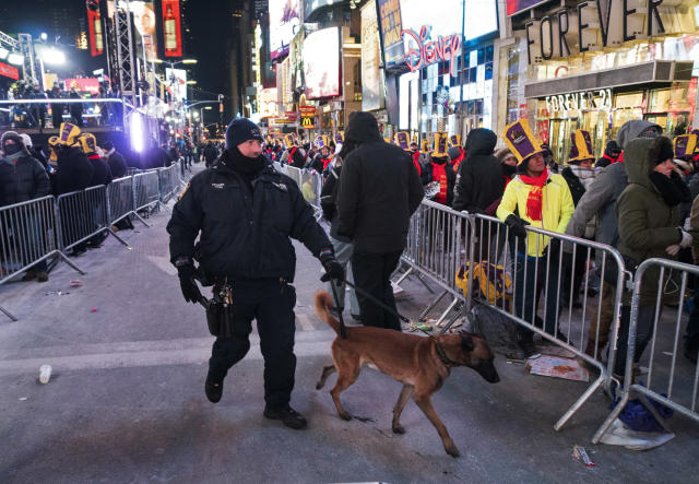 <p>A New York City canine police officer walks past revelers gathered on Times Square in New York Sunday, Dec. 31, 2017, during a New Year's Eve celebration. (Photo: Craig Ruttle/AP) </p>