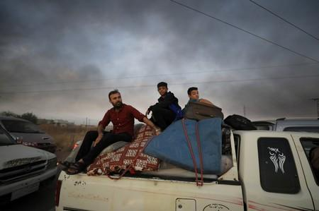 FILE PHOTO: People sit on belongings at a back of a truck as they flee Ras al Ain town