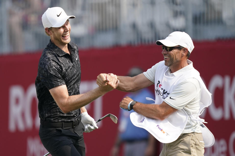 Cam Davis of Australia jubilates with his caddie after scoring an eagle on the 17th green from the sand during the final round of the Rocket Mortgage Classic golf tournament, Sunday, July 4, 2021, at the Detroit Golf Club in Detroit. (AP Photo/Carlos Osorio)