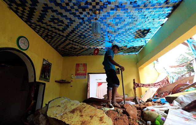 <p>A Sri Lankan mudslide survivor salvages belongings at a destroyed house in Kiribathgala, in Ratnapura district, Sri Lanka, Monday, May 29, 2017. (AP Photo/Eranga Jayawardena) </p>
