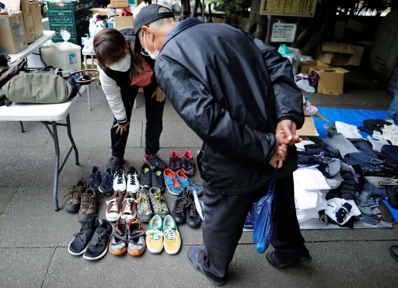 A volunteer takes part in shoes and clothes aid handouts for the needy, as the spread of the coronavirus disease (COVID-19) continues in Tokyo