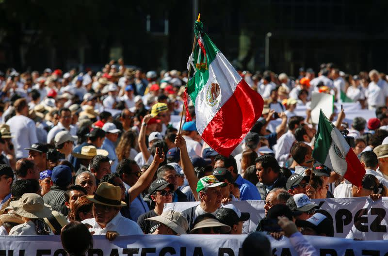 Demonstrators hold up a Mexican flag during a march to protest against violence on the first anniversary of President Andres Manuel Lopez Obrador taking office, in Mexico City
