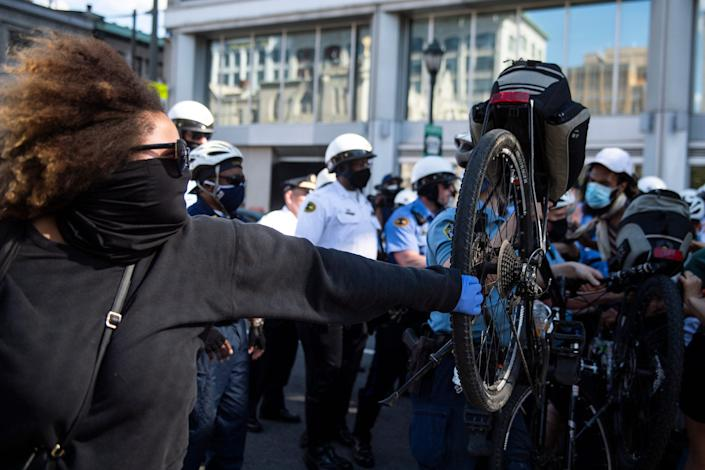 Police officers use bicycles to push back a crowd of demonstrators Saturday in Philadelphia.