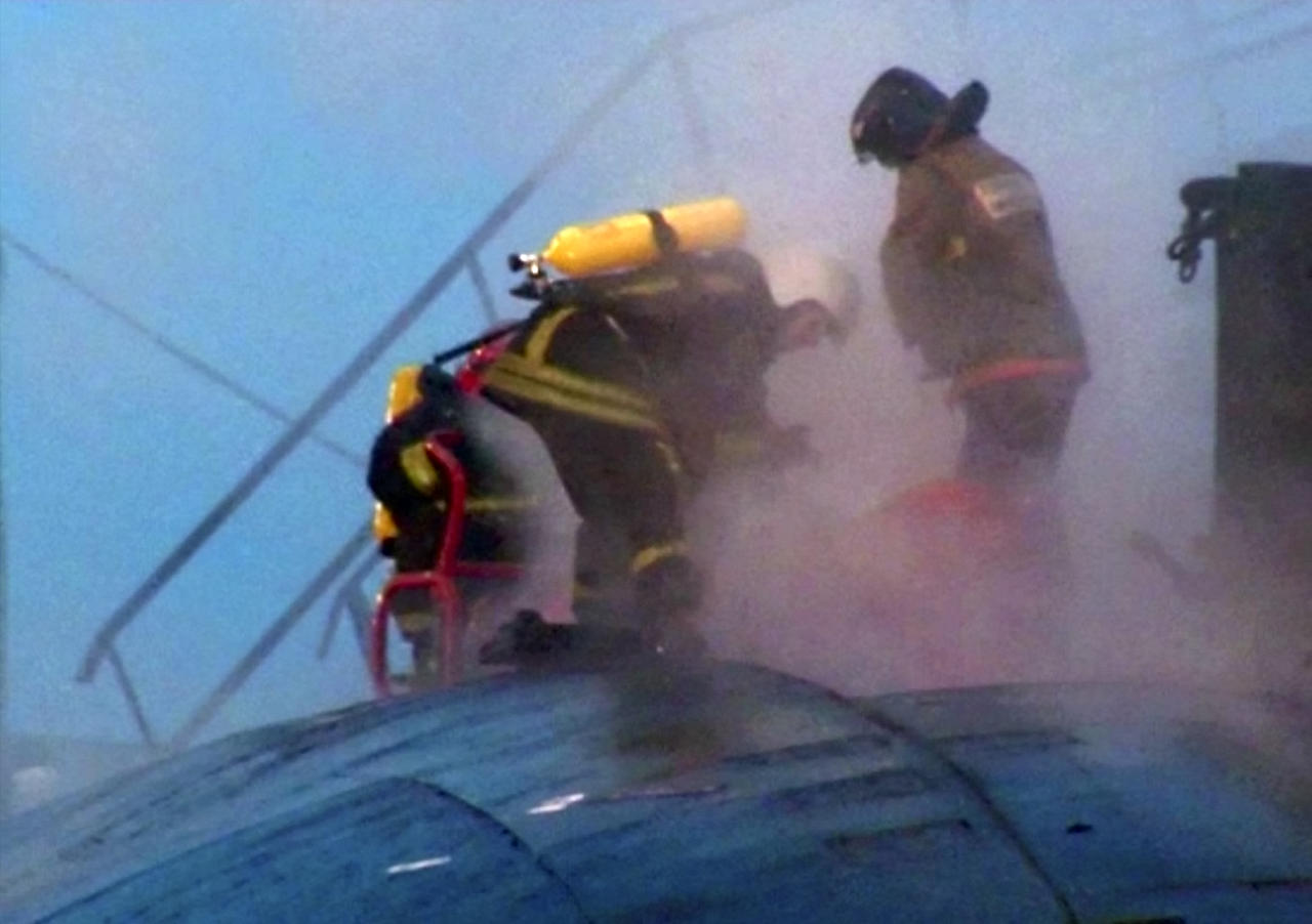 In this video image from Ru-RTR Russian state television channel, firefighters work on the hull of the Yekaterinburg nuclear submarine in a dock at the Roslyakovo shipyard in the Murmansk region, Russia, Friday, Dec. 30, 2011. A fire that erupted while the Yekaterinburg was in drydock for repairs at the town of Roslyakovo near Murmansk has left seven crewmembers injured after they inhaled poisonous fumes from the blaze. (AP Photo/Ru-RTR Russian state channel/ Via APTN)