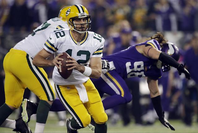 Green Bay Packers quarterback Aaron Rodgers (12) runs in the first half of an NFL football game against the Minnesota Vikings, Sunday, Oct. 27, 2013, in Minneapolis. (AP Photo/Jim Mone)