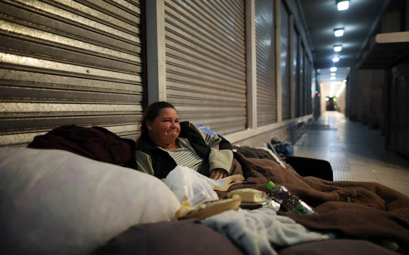 Homeless woman on blankets outdoors - Natacha Pisarenko/AP Photo