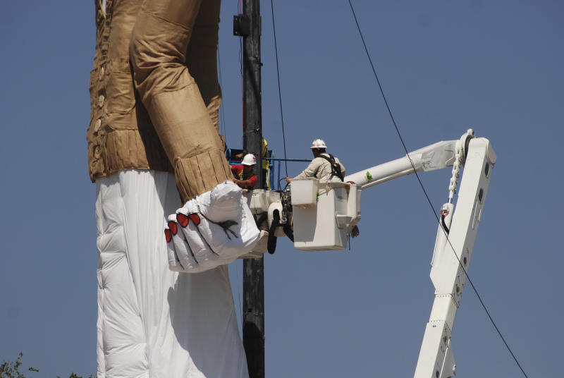 Workers prepare the towering Zozobra marionette for its annual burning at a city park in Santa Fe, N.M., on Friday, Sept. 1, 2017. High anxiety about White House politics, hurricane flooding and even the threat of nuclear war with North Korea is adding an extra spark to the annual destruction of the effigy to gloom and doom. Inside the six-story puppet are reams of crumpled, handwritten notes about recent troubles and travails that people hope to leave behind. (AP Photo/Morgan Lee)