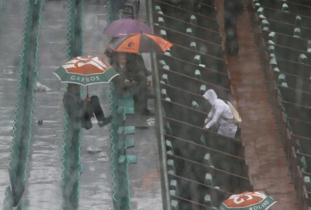 Spectators protect themselves from rain during a men's singles match between Novak Djokovic of Serbia and Joao Sousa of Portugal at the French Open tennis tournament at the Roland Garros stadium in Paris May 26, 2014. REUTERS/Gonzalo Fuentes (FRANCE - Tags: SPORT TENNIS)