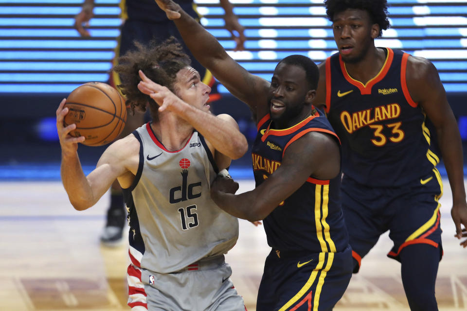 Washington Wizards center Robin Lopez, left, looks for a shot against Golden State Warriors forward Draymond Green during the first half of an NBA basketball game in San Francisco, Friday, April 9, 2021. (AP Photo/Jed Jacobsohn)