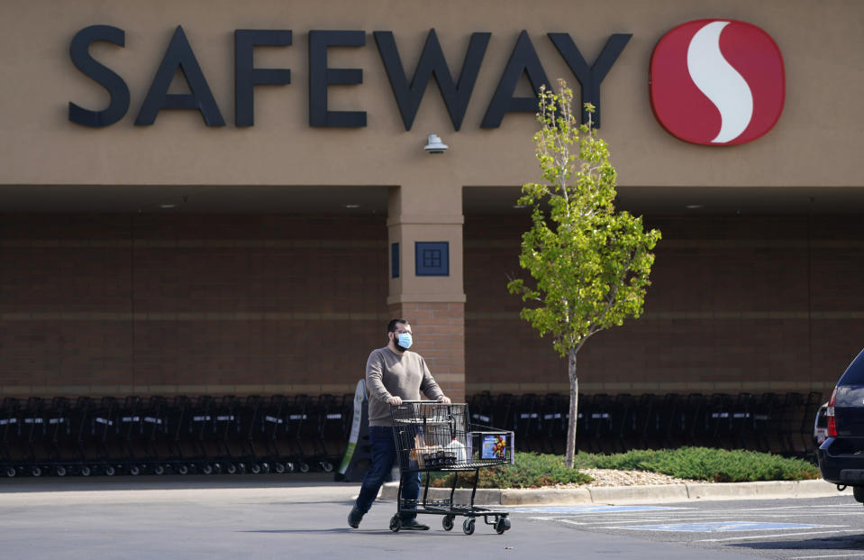 In this Wednesday, May 19, 2021, photograph, a shopper wearing a face covering uses a cart to wheel his purchases to a vehicle at a Safeway grocery store in Aurora, Colo. Many workers in retail sales jobs who are fully vaccinated are now concerned about risks posed as retailers change their mask-wearing policies for customers. (AP Photo/David Zalubowski)