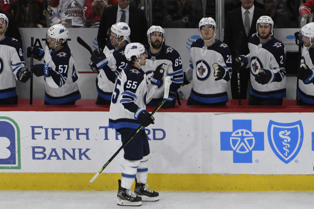 Winnipeg Jets center Mark Scheifele (55) celebrates his goal against the Chicago Blackhawks with his teammates during the second period of an NHL hockey game Sunday, Jan. 19, 2020, in Chicago. (AP Photo/David Banks)
