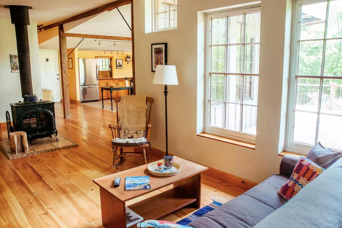 <p>The kitchen opens up to the cozy living room with this traditional wood-burning fireplace. (Airbnb) </p>