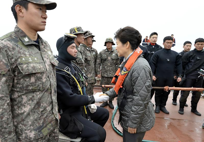 South Korean President Park Geun-hye, right, shakes hands with a diver at the site where the Sewol ferry sank in waters off the southern coast near Jindo, South Korea, Sunday, May 4, 2014. Park told families of those missing in the sunken ferry that her heart breaks knowing what they are going through, as divers recovered two more bodies on Sunday. (AP Photo/Yonhap) KOREA OUT
