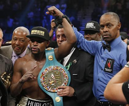 Floyd Mayweather (L) poses with referee Kenny Bayless after his win over Manny Pacquiao. (AP)