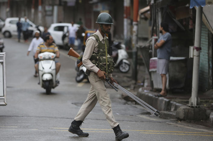 A paramilitary soldier walks on a street in Jammu, India, Friday, Aug. 9, 2019. The restrictions on public movement throughout Kashmir have forced people to stay indoors and closed shops and even clinics. All communications and the internet have been cut off. Prime Minister Modi said late Thursday the situation in the region would return to normal gradually. (AP Photo/Channi Anand)