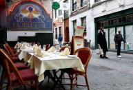 People past an empty terrace of a restaurant amid the coronavirus disease outbreak in Brussels