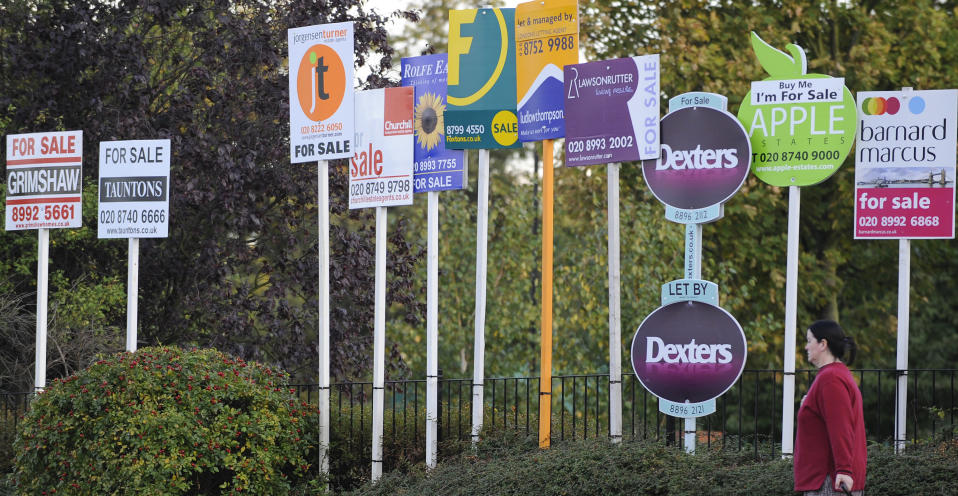 A woman passes property signs, in west London. Photo: Toby Melville/Reuters
