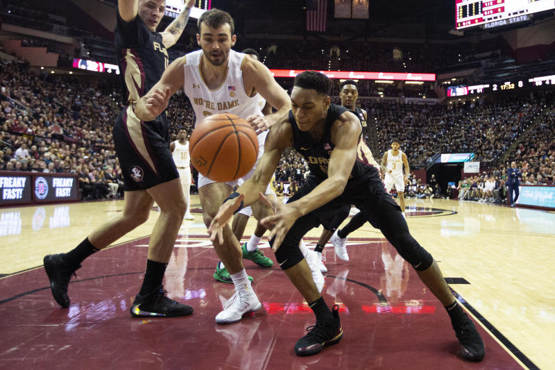 Florida State guard Devin Vassell (24) and Notre Dame forward John Mooney (33) battle for the ball in the first half of an NCAA college basketball game in Tallahassee, Fla., Saturday, Jan. 25, 2020. (AP Photo/Mark Wallheiser)