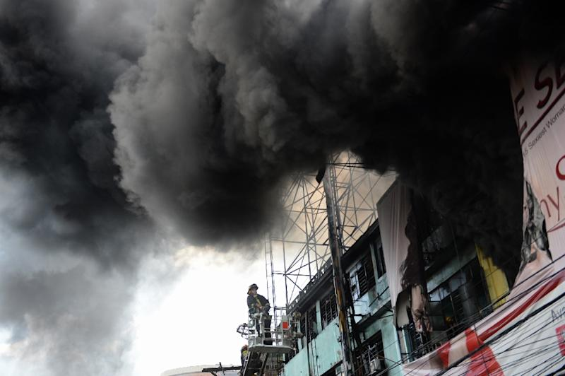 A fireman stands on a ladder as thick black smoke engulfs streets and buildings after a fire hit a shanty town in Manila on December 4, 2015 (AFP Photo/Ted Aljibe)