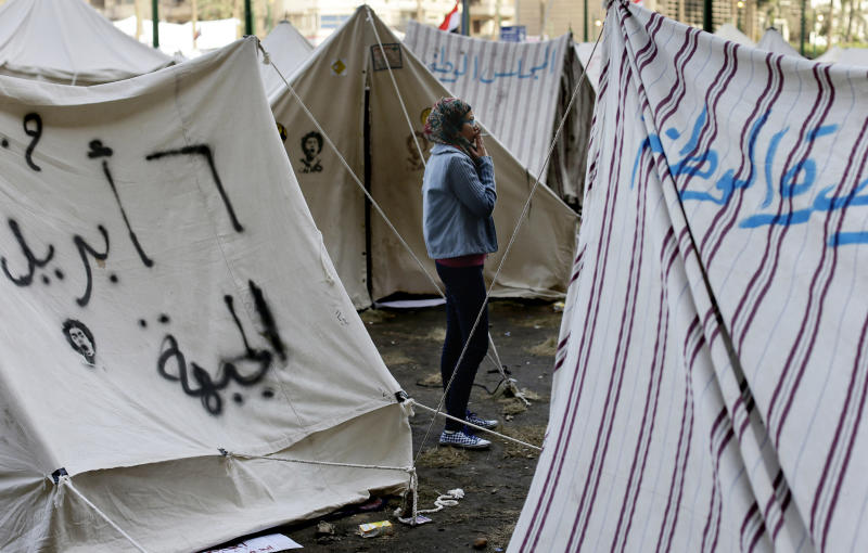 An Egyptian protester smokes a cigaret outside her tent in Tahrir square in Cairo, Egypt, Sunday, Dec. 9, 2012. Egypt's liberal opposition has called for more protests on Sunday after the president made concessions overnight that fell short of their demands to rescind a draft constitution going to a referendum on Dec. 15. (AP Photo/Hassan Ammar)
