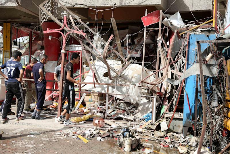 Civilians inspect the aftermath of a car bomb attack in the crowded commercial area of Karrada, in Baghdad, Iraq, Friday, April 18, 2014. Authorities in Iraq say a car bomb targeted a street full of shoppers in the capital. in Baghdad on Thursday. (AP Photo/Karim Kadim)