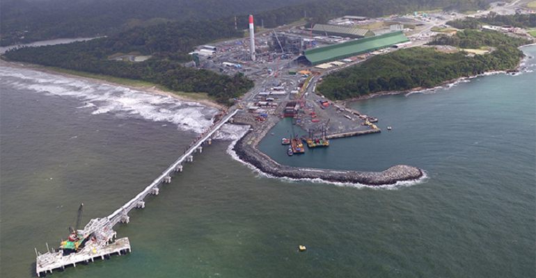 Mine refining facility on a coastline with a terminal jutting into the water.