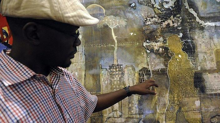 Kenyan painter Paul Odete looks at his work displayed at the first commercial auction of East African art on November 4, 2013 in Nairobi, on the eve of the auction.