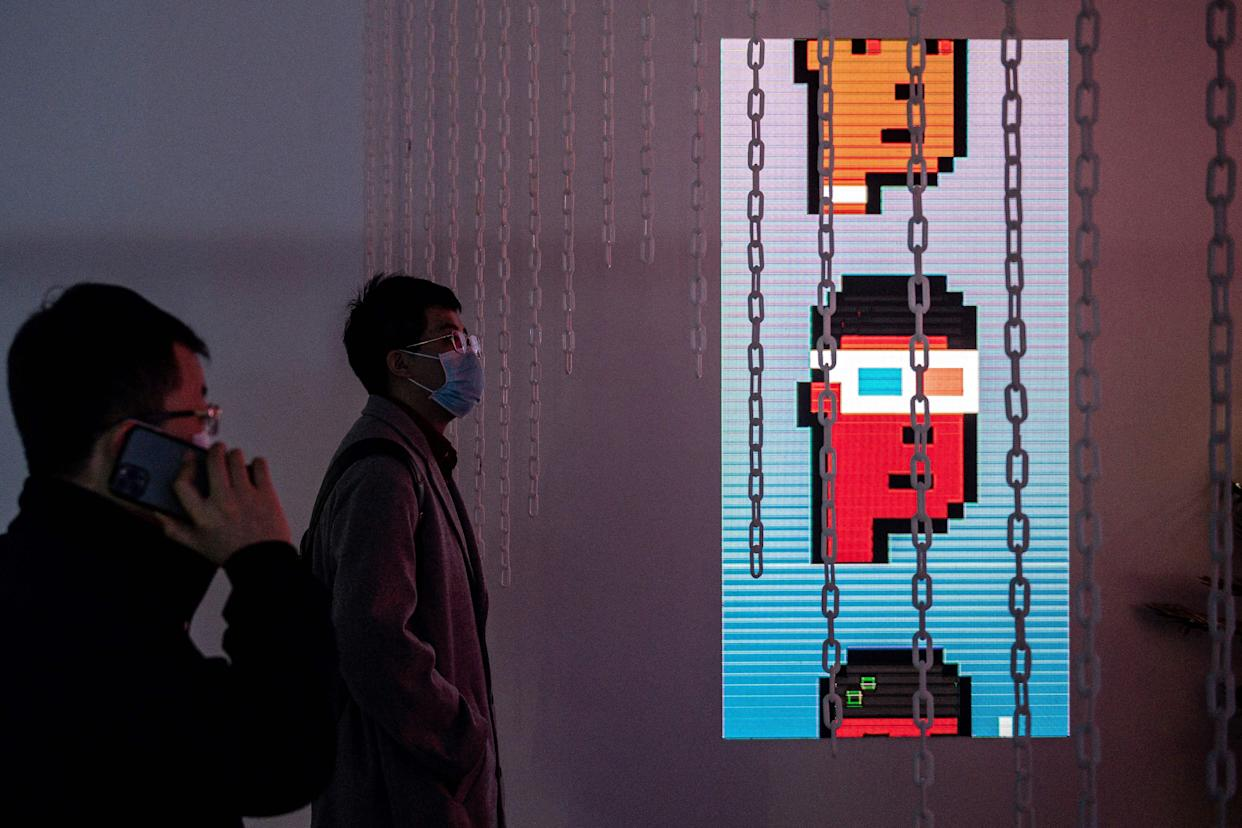 People look at CryptoPunks digital characters (R) at a crypto art exhibition entitled Virtual Niche: Have You Ever Seen Memes in the Mirror?, one of the world's first physical museum shows of blockchain art, ahead of its opening in Beijing on March 26, 2021. - RESTRICTED TO EDITORIAL USE - MANDATORY MENTION OF THE ARTIST UPON PUBLICATION - TO ILLUSTRATE THE EVENT AS SPECIFIED IN THE CAPTION (Photo by NICOLAS ASFOURI / AFP) / RESTRICTED TO EDITORIAL USE - MANDATORY MENTION OF THE ARTIST UPON PUBLICATION - TO ILLUSTRATE THE EVENT AS SPECIFIED IN THE CAPTION / RESTRICTED TO EDITORIAL USE - MANDATORY MENTION OF THE ARTIST UPON PUBLICATION - TO ILLUSTRATE THE EVENT AS SPECIFIED IN THE CAPTION (Photo by NICOLAS ASFOURI/AFP via Getty Images)