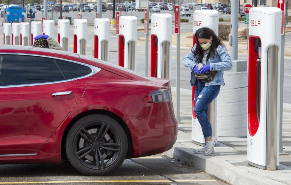 A woman prepares to plug in her electric vehicle