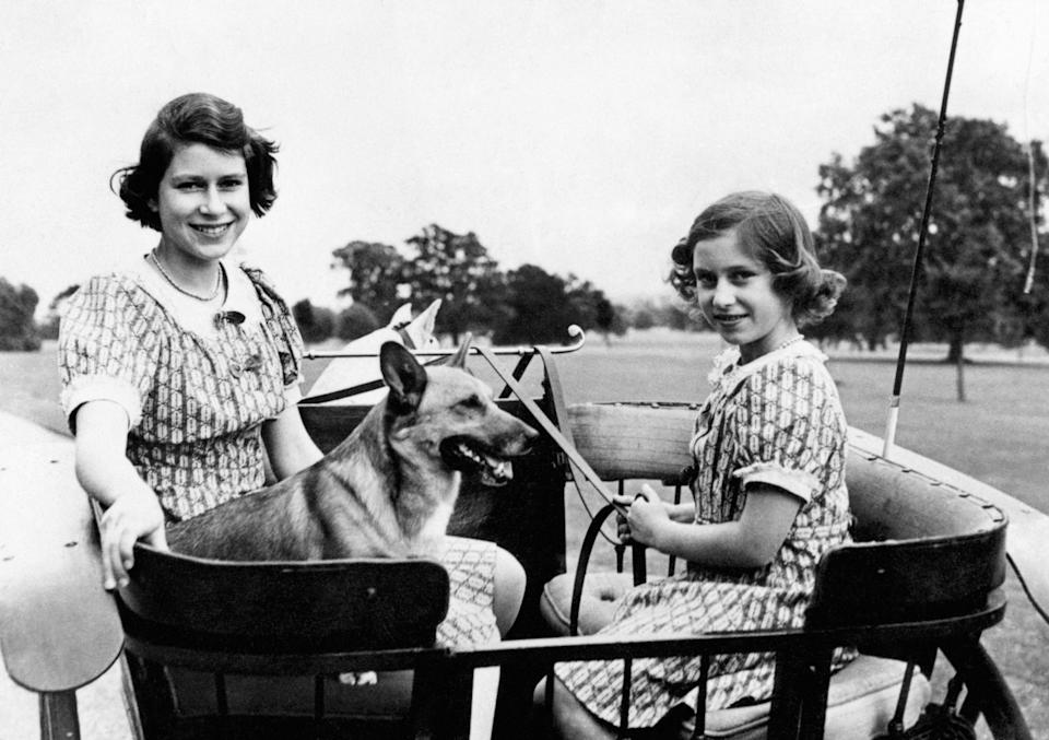 <p>Princess Elizabeth and Princess Margaret ride a ponycart in the garden of their wartime country residence (Windsor) (PA Archive) </p>