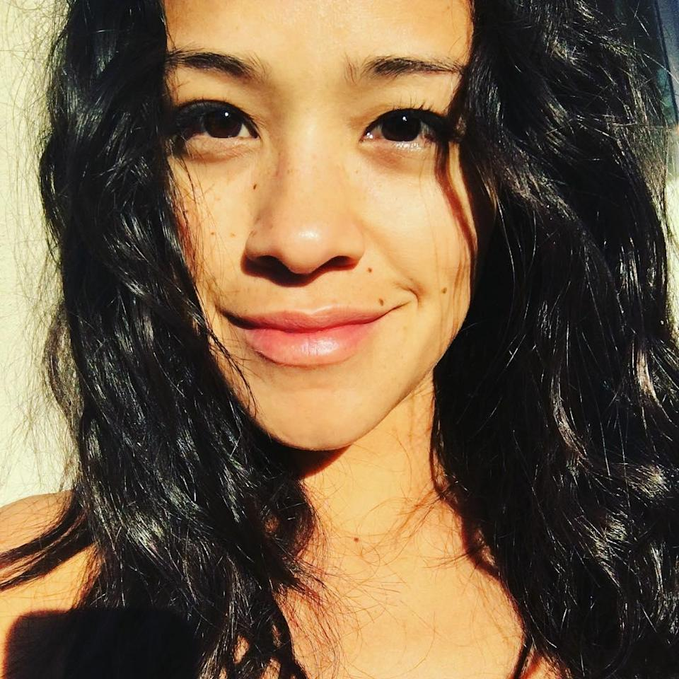 """Gina captioned this photo, """"Sun kissed. No makeup. Messy hair. Me. Here's to a badass day 🙌🏽❤️."""" (And here's to her beautifully glowing skin.)"""