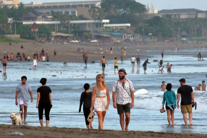 FILE PHOTO: Tourists walk on a beach as the government extends restrictions to curb the spread of coronavirus disease (COVID-19) in Badung