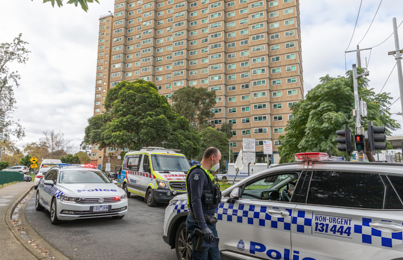 Police cars and officers outside one of the locked-down towers in Melbourne