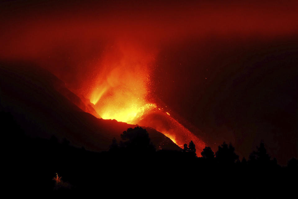 A view of the volcano continues to spew out lava on the Canary island of La Palma, Spain in the early hours of Sunday, Oct. 10, 2021. A new river of lava has belched out from the La Palma volcano, spreading more destruction on the Atlantic Ocean island where molten rock streams have already engulfed over 1,000 buildings. The partial collapse of the volcanic cone has sent a new lava stream heading toward the western shore of the island. (AP Photo/Daniel Roca)