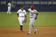 Cincinnati Reds' Aristides Aquino (44) celebrates as he heads to third base past Miami Marlins third baseman Starlin Castro (13) after hitting a home run scoring Eugenio Suarez and Joey Votto during the first inning of a baseball game, Wednesday, Aug. 28, 2019, in Miami. (AP Photo/Wilfredo Lee)