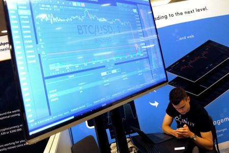 FILE PHOTO: FILE PHOTO: A man works beneath a display showing the market price of Bitcoin on the floor of the Consensus 2018 blockchain technology conference in New York City