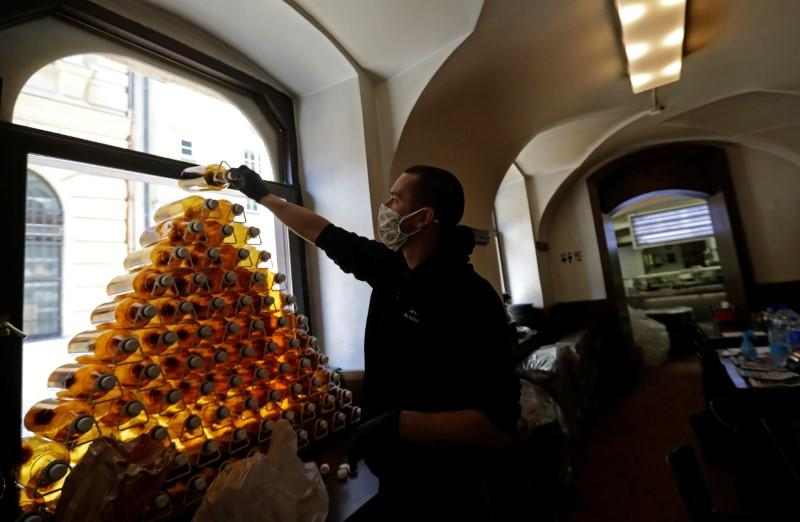 A bartender prepares plastic bottles inside of a closed pub in Prague
