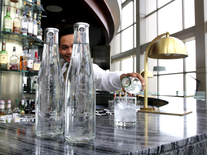 This undated image provided by Hyatt shows a water station with reusable water bottles. Hyatt Hotels Corp. is the latest hotel company to remove small bottles from its bathrooms in an effort to reduce waste. Hyatt is also cutting down on the use of plastic water bottles at meetings and events and increasing the number of water stations in its hotels so guests can refill their own water bottles. (Courtesy of Hyatt via AP)