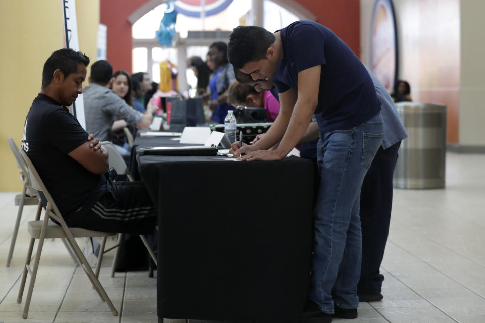 Billy Ramos, right, fills out a job application with Adidas during a job fair at Dolphin Mall, Tuesday, Oct. 1, 2019, in Miami. (AP Photo/Lynne Sladky)
