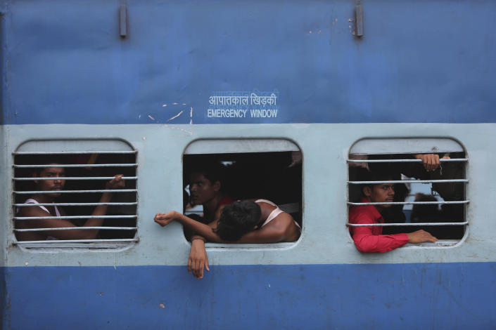 Indian migrant laborers sit inside a train as they prepare to leave the region, at a railway station in Jammu, India, Wednesday, Aug. 7, 2019. Indian lawmakers passed a bill Tuesday that strips statehood from the Indian-administered portion of Muslim-majority Kashmir, which remains under an indefinite security lockdown, actions that archrival Pakistan warned could lead to war. (AP Photo/Channi Anand)