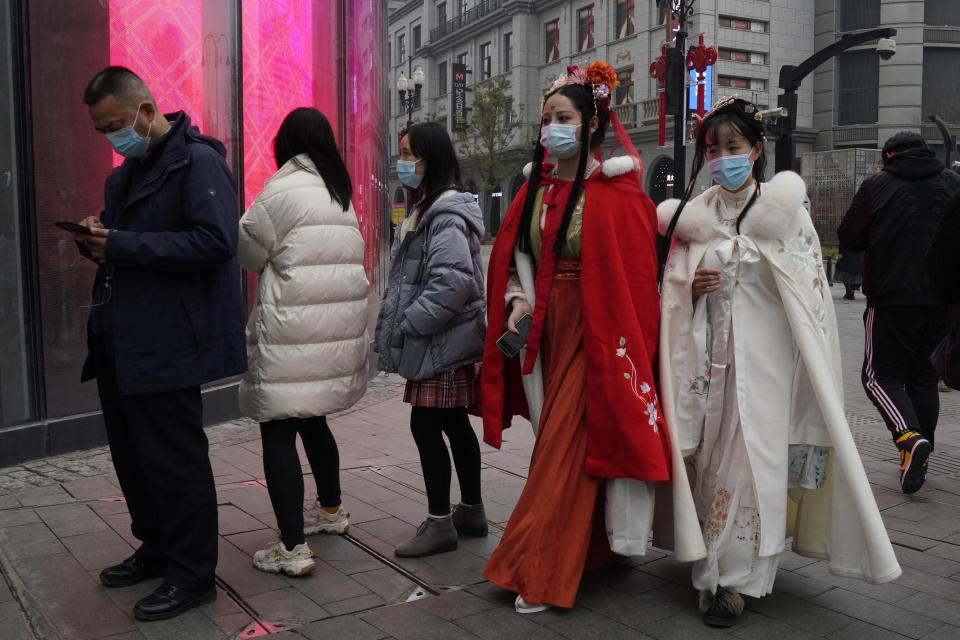 Chinese women dressed in traditional costumes and wearing masks visit a popular shopping street in Wuhan in central China's Hubei province, Saturday, Jan. 23, 2021. A year after it was locked down to contain the spread of coronavirus, the central Chinese city of Wuhan has largely returned to normal, even as China continues to battle outbreaks elsewhere in the country. (AP Photo/Ng Han Guan)