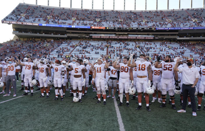 Texas players stand on the football field in front of socially distanced fans in stands.
