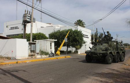"""A soldier atop a vehicle is seen outside the Forensic Medical Service (SEMEFO) after the arrival of the body of Francisco Zazueta, also known as """"Pancho Chimal,"""" in Culiacan"""