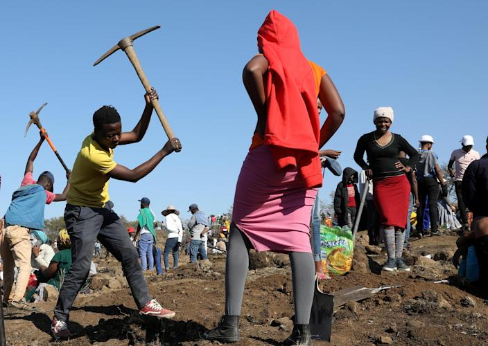 A person uses a pickaxe to dig as fortune seekers flock to the village after pictures and videos were shared on social media showing people celebrating after finding what they believe to be diamonds, in the village of KwaHlathi, outside Ladysmith, in KwaZulu-Natal province, South Africa, June 14, 2021. / Credit: Siphiwe Sibeko/REUTERS