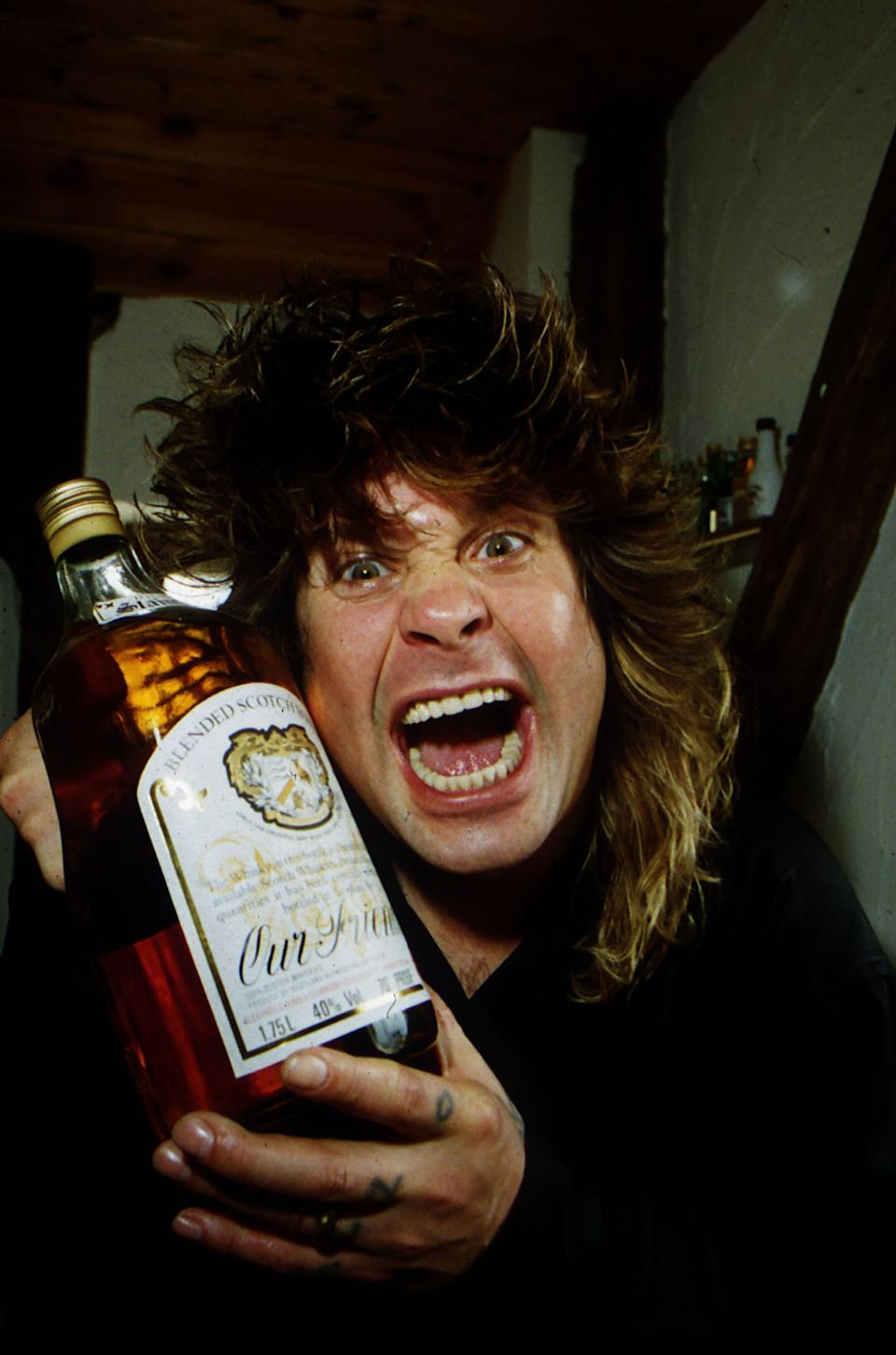 Ozzy Osbourne holding a large bottle of whisky at his home, May 1989. (Photo by People/Mirrorpix/Getty Images)
