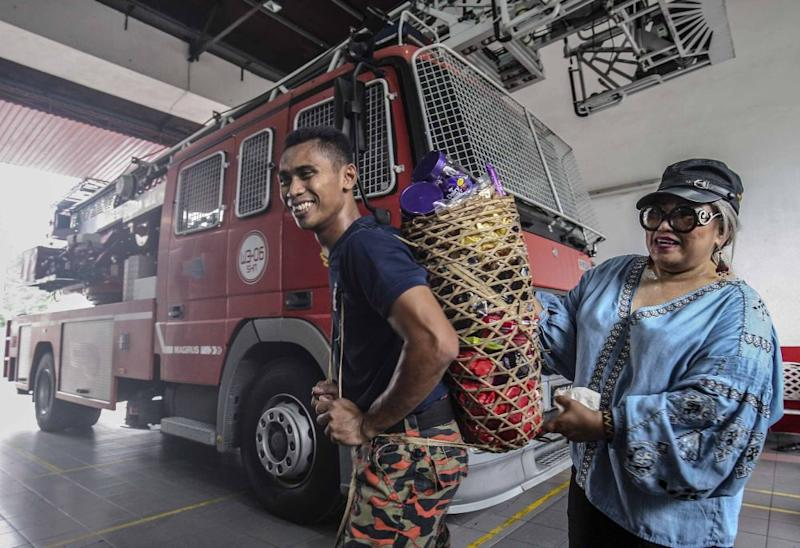 A fire and rescue personnel from the Sri Hartamas Fire and Rescue station receives chocolates from lawyer and activist Siti Kasim, May 26, 2018.